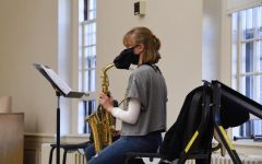 A UVM Concert Band member plays the saxophone through a mask with a mouth hole in it, Oct. 14 in a class led by music professor Dr. Thomas Turner.