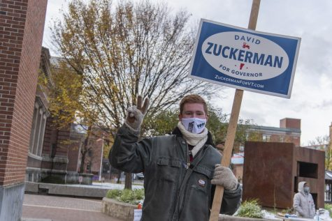 Senior Aidan Doherty stands outside the Fletcher Free Library on Nov. 3 holding up a David Zuckerman campaign sign as he thanks students for voting. Doherty is a member of the UVM College Democrats.