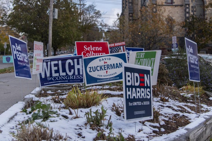 Campaign signs fill a patch of snow covered grass outside the Fletcher Free Library Nov. 3, where UVM Campus Democrats stood outside congratulating students for voting throughout the day.