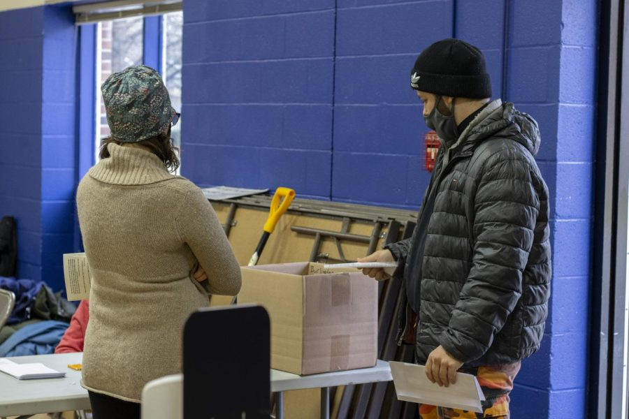 A man stands at the beginning of the check-in line for Ward 1s polling station Nov. 3. His mask falls beneath his nose as he talks to the volunteer checking him in.