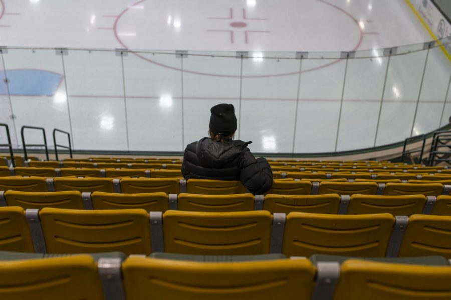 Sophomore Cameron Morrisey, member of the women's hockey team, sits alone in Gutterson Fieldhouse stands.