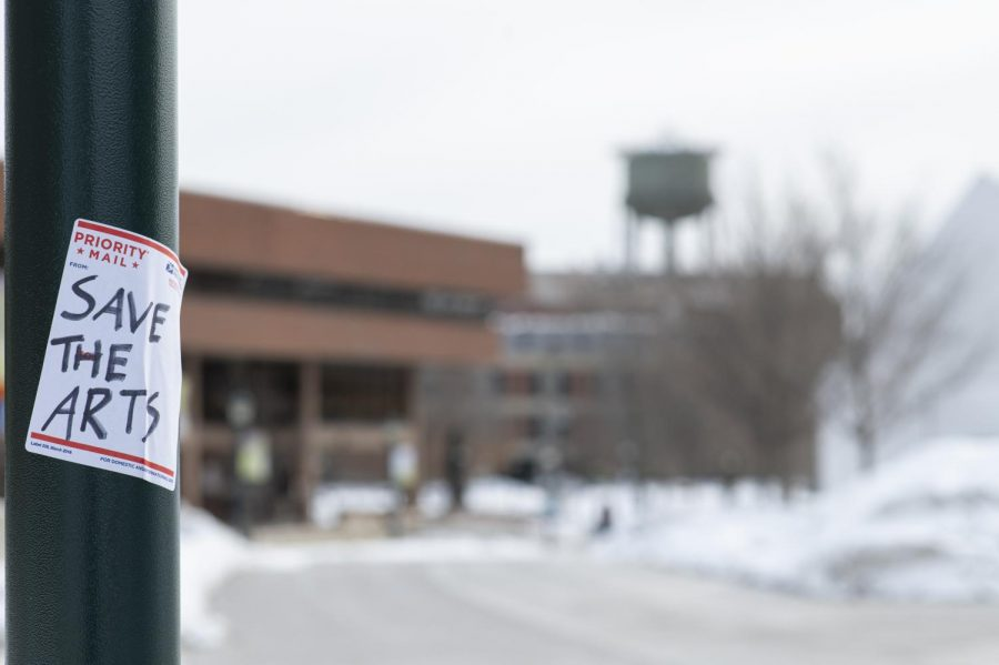 "A USPS sticker with ""Save the Arts"" is stuck to a UVM streetlamp next to Rally cat Feb. 9. Similar stickers with different messages pertaining to the recent CAS budget cuts have appeared on other streetlamps around campus."