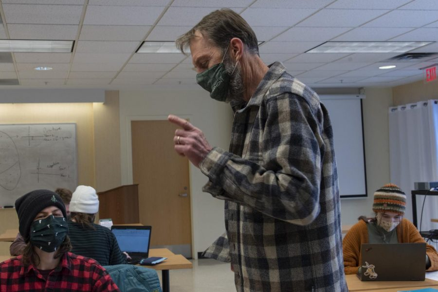 UVM Geology professor Stephen Wright crouchs between two of his students as he teaches during their lab Feb. 10. Wright is one of three other College of Arts and Sciences professors who have recently been laid off due to the budget cuts.