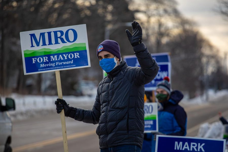 "Burlington Mayoral incumbent Miro Weinberger stands on North Ave during a ""honk and wave"" with his supporters Feb. 19. As cars passed by they honked in support."