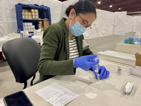 UVM Medical Center Pharmacist Julie Finnigan extracts the Pfizer COVID vaccine from a vile.