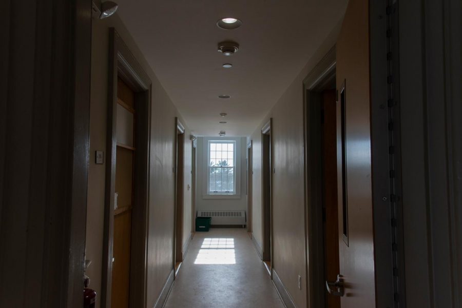 An empty hallway on the second floor of Slade Hall shows no sign of the students who are quarantining behind the doors.