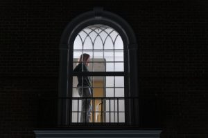 Ella Ruehsen, a UVM sophomore and assistant news editor for the Cynic stands at the center window of Slade Hall Feb. 13. Slade Hall is a residence hall on Redstone Campus which has been reserved for COVID positive students.