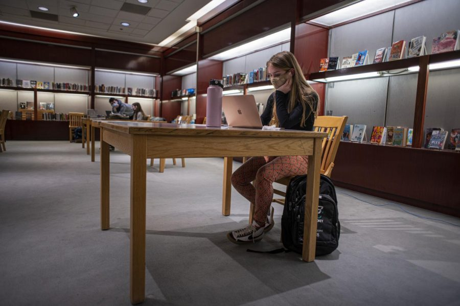 A student sits in the library working on her homework March 16.