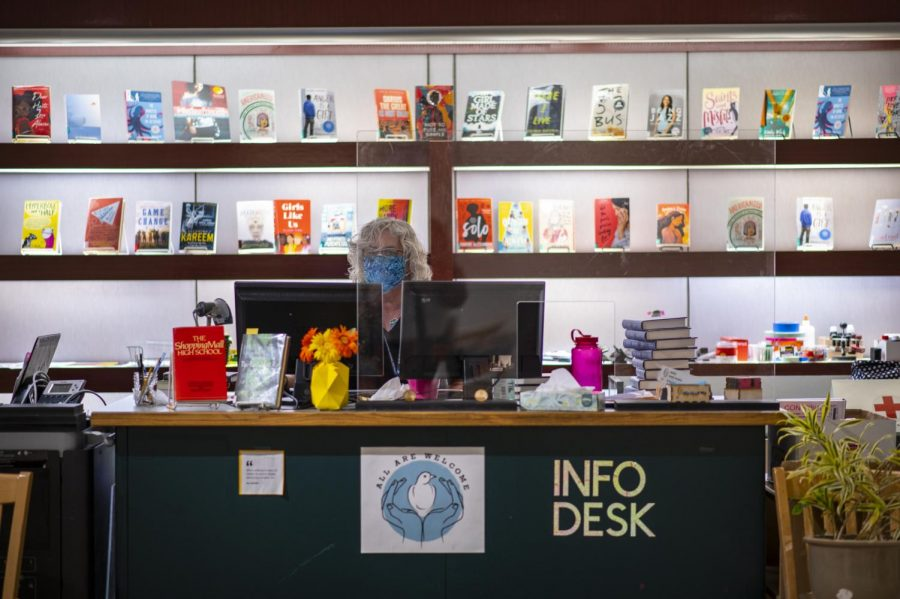 Ellen Wollensack, Library Assistant sits behind the check out desk March 16.