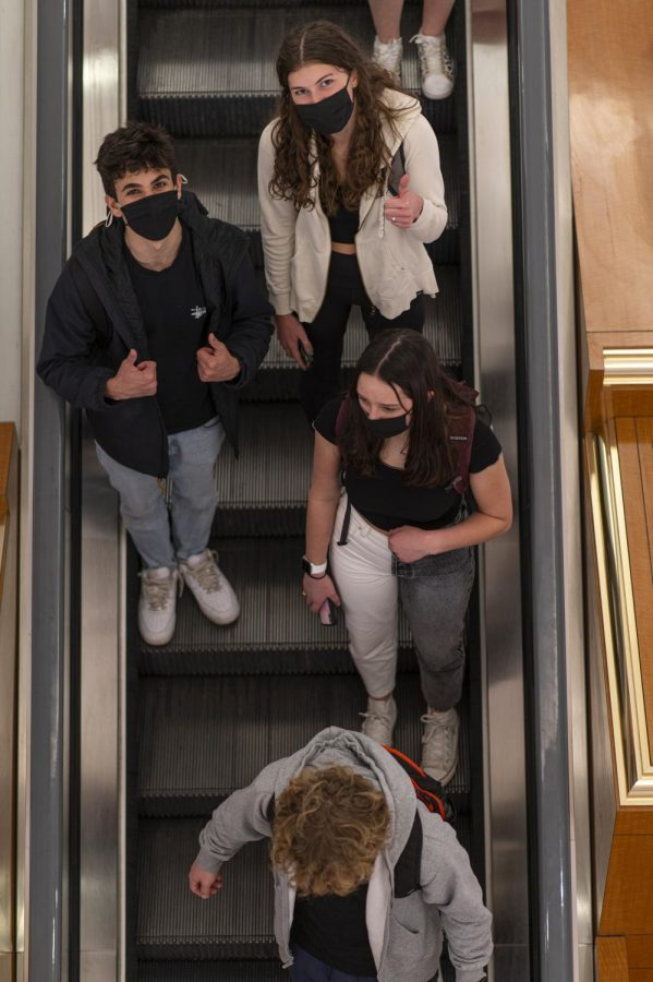 Students take the escalator down to the exit as they leave school after their last class March 16