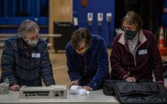 Three Ward 1 election inspectors review the ballot receipt before sealing it inside the tabulation bag March 2.