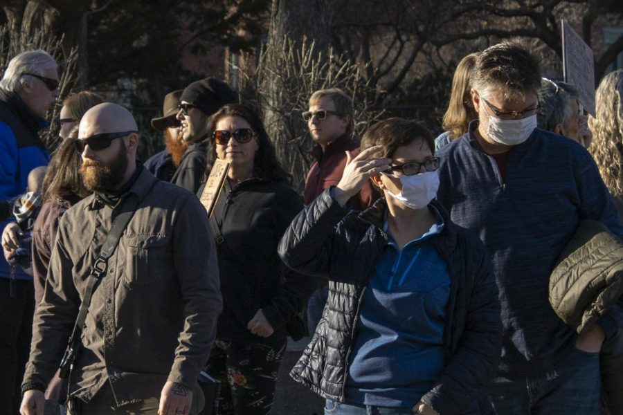 Pedestrians stand with their heads facing the other way as anti-mask protestors surround them at the crosswalk from Pearl street to Church street March 20.