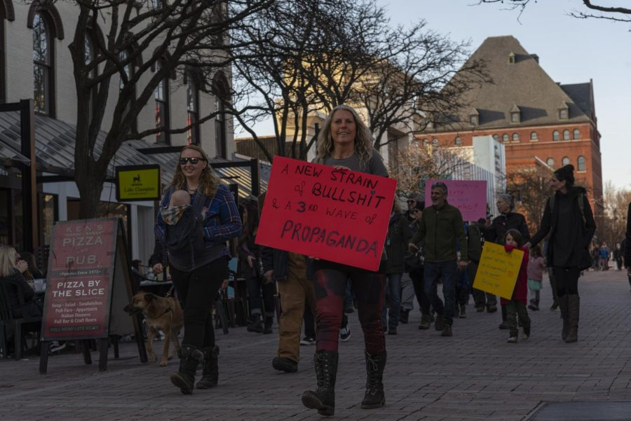 A woman leads the group of anti-mask protestors down Church street March 20.