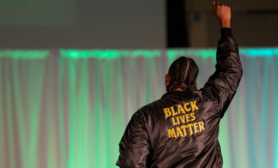 Senior Eddie Travieso holds up his fist in Fruition's Black Lives Matter bomber jacket Feb. 27.