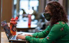 Sophomore Althea Deschenes sits in the Davis Center doing homework while wearing double masks Feb. 19.