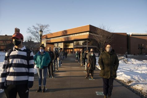 Masked students stand in lines outside the COVID-19 testing center.