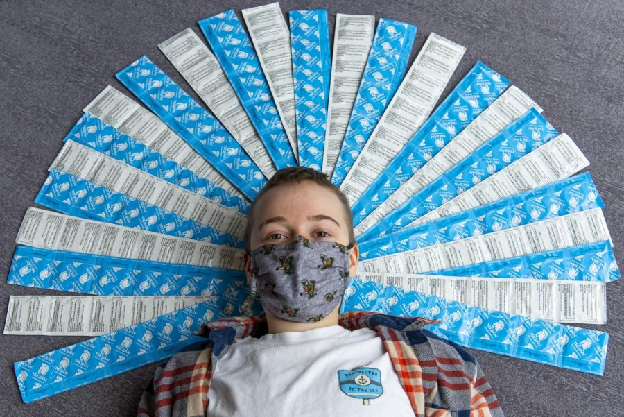 Freshman Elene Karlberg, known as UVM Condom Kid, poses surrounded by over 100 Trojan condoms March 31.