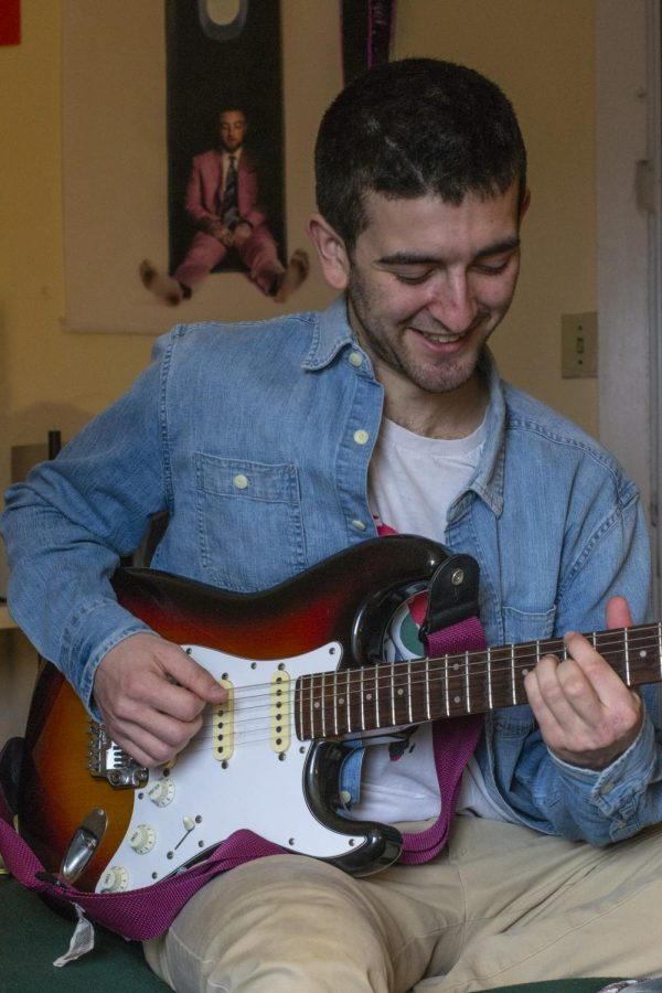 Luban sits playing his guitar in front of a Mac Miller poster April 2.