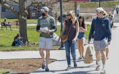 The family of a prospective student walks through Andrew Harris Commons without observing proper masking protocols April 10.