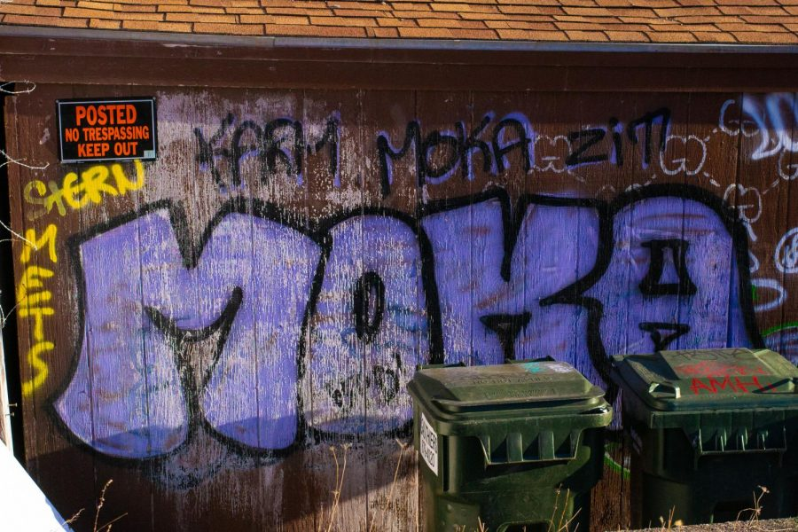 Graffiti tags are painted on the side of a shed with a 'No Trespassing' sign April 8.