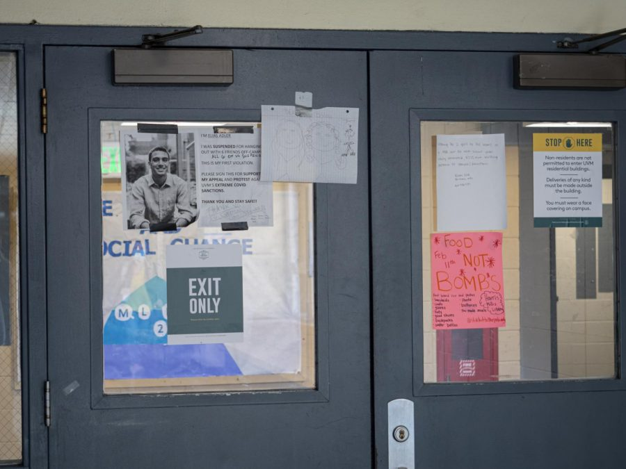 Doors leading to Millis dorms are covered in various signs including a message from a student who had been recently suspended for breaking the Green and Gold Promise.
