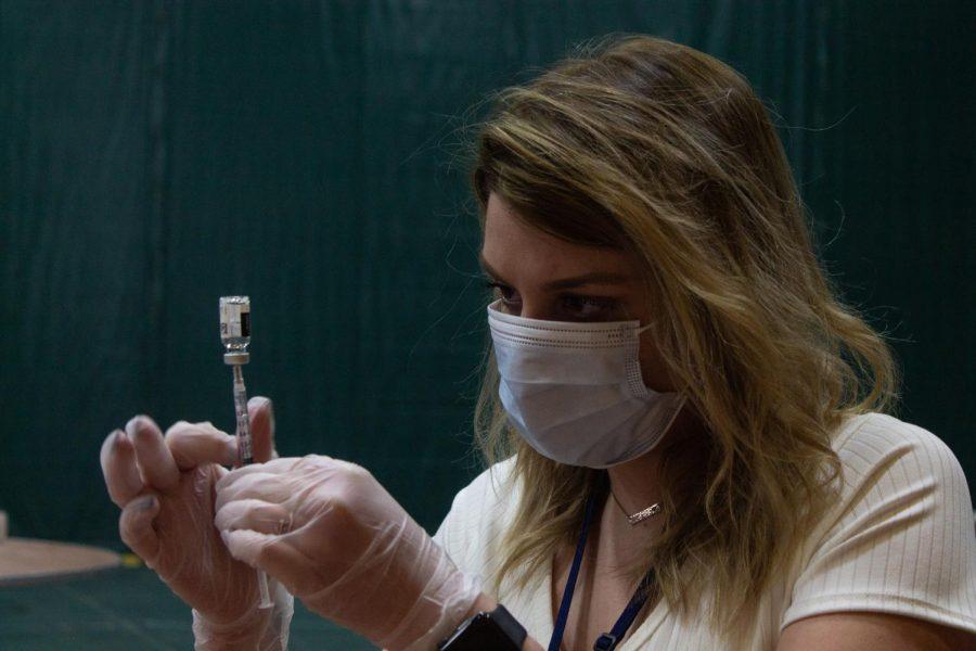 A Walgreens employee fills a syringe May 2.