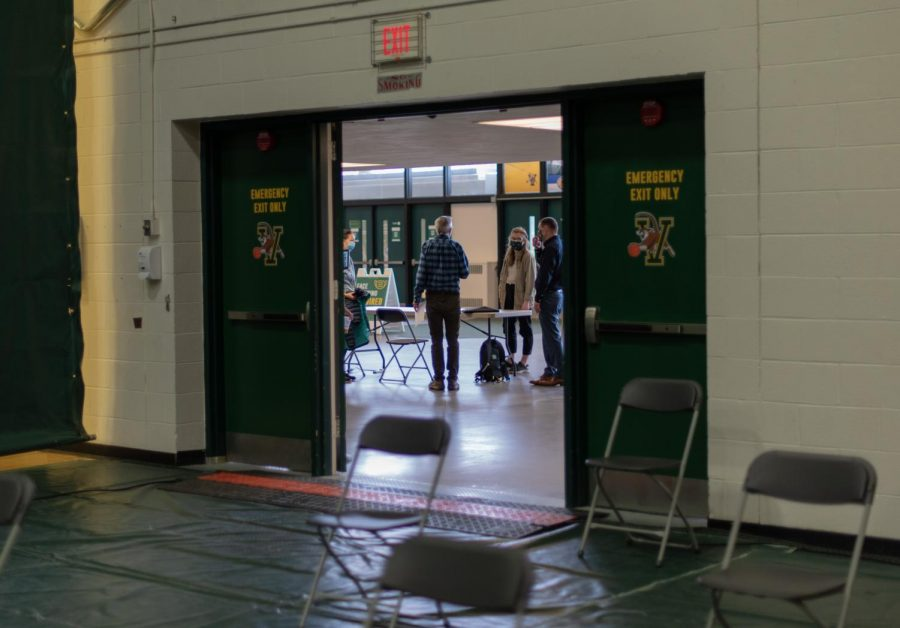 Workers gather to finish preparing for the COVID-19 vaccine clinic before students arrive May 2.