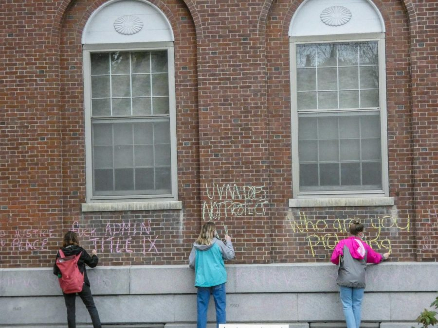 Student supporters write messages on the walls of the Waterman building in chalk directed towards the UVM administration and the Title IX office May 3.