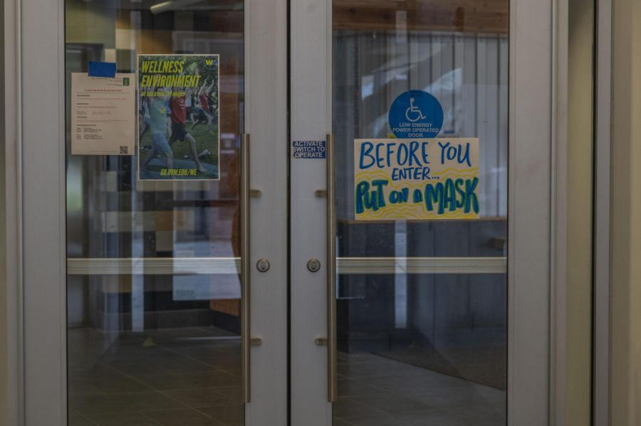 A sign reminds students to put their masks on before they enter Aug. 28.