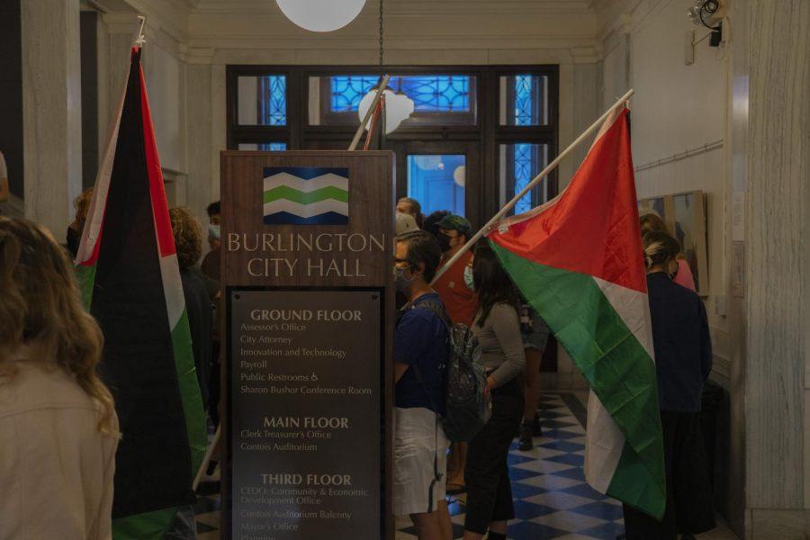 Protestors hold Palestinan flags inside the foyer of Burlington City Hall.