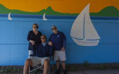 Cancer survivor Steve Milizia, his wife and son pose in front of a mural that memorializes his experiences with Sail Beyond Cancer.