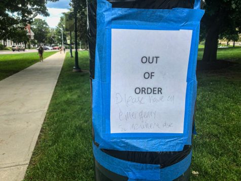 An out of order sign on a Blue Light post has a messages written on it stating Please have an emergency somewhere else.