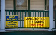 Signs advertise apartments for rent on College Street.